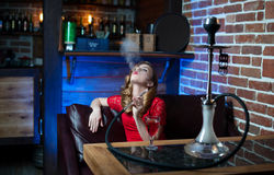 A beautiful girl in a red evening dress smokes a hookah in the interior of a loft-style bar Royalty Free Stock Image