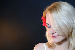 Beautiful girl with a red flower in her hair Royalty Free Stock Images