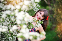 Beautiful girl with red flower on her head in the spring garden Stock Photo