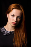 Beautiful girl. With red hair on a black background Royalty Free Stock Photo