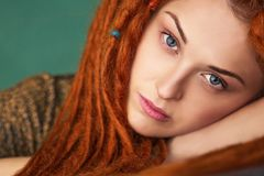 Beautiful girl with red hair and blue eyes, close-up portrait. Beautiful and intelligent girl with red dreadlocks and blue eyes is sad, close-up portrait Stock Images