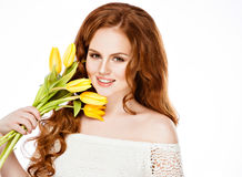 Beautiful girl with red hair in a braid, holds yellow tulips on Royalty Free Stock Image