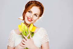 Beautiful girl with red hair in a braid, holds yellow tulips wit Stock Photo