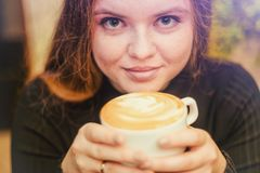 Beautiful girl with red hair and freckles drinking coffee portrait stock photos