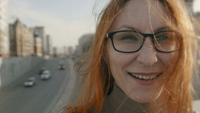 Beautiful girl with red hair in glasses at street near highway looks in camera Royalty Free Stock Photography