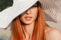 Beautiful girl with red hair with a hat on his head. Beach summer time Stock Photo