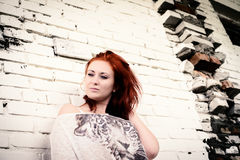 Beautiful girl with red hair outdoor against brick wall Stock Photo