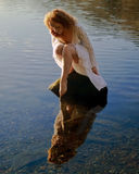 Beautiful girl with red hair reflected in ripples and still water Royalty Free Stock Photos
