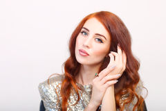 Beautiful girl with red hair and shiny dres Stock Image