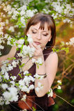 Beautiful girl with red hair in spring cherry garden Stock Photos