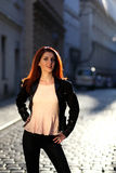 Beautiful girl with red hair on the street. Young woman in leggings in evening light stock photos