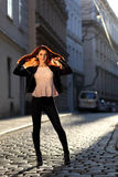 Beautiful girl with red hair on the street. Young woman in leggings and high heels in evening light Royalty Free Stock Photos