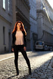 Beautiful girl with red hair on the street. Young woman in leggings and high heels in evening light Royalty Free Stock Photography