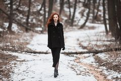 Beautiful girl with red hair. Striking girl with long red hair in black clothes. A woman in a black coat posing on a background of winter, autumn nature. Female Stock Photo