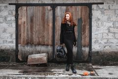 Beautiful girl with red hair. Striking girl with long red hair in black clothes. A woman in a black coat and backpack in hands posing on the background of old Royalty Free Stock Photo