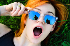 The beautiful girl with red hair and wearing spectacles lies pos. Es lying on a grass.The model Stock Photos