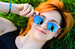 The beautiful girl with red hair and wearing spectacles lies pos. Es lying on a grass.The model Royalty Free Stock Photography