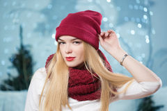 Beautiful girl in a red hat at a Christmas garland Stock Photos