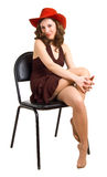 Beautiful girl in a red hat sits on a chair Stock Images