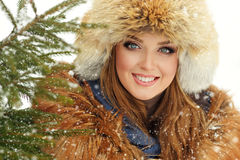 Beautiful girl in a red hat smiling winter when it snows.  stock photos