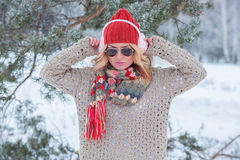 Beautiful girl in a red hat and sweater in the snow in pink with headphones and scarf Royalty Free Stock Photos