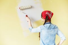 Beautiful girl in red Headband painting the wall with paint roll Royalty Free Stock Photos