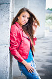 Beautiful Girl in Red Jacket. Standing near wall, touching her hair with left hand stock photo