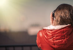 Beautiful girl in a red jacket and headphones. A girl on the balcony listening to music and is singing Stock Photo