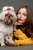 Beautiful girl with red lips and adorable Shih-tzu dog. Beautiful brunette girl in yellow with red lips and adorable Shih-tzu dog on dark background in studio stock image
