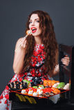 Beautiful girl with red lips eating sushi close-up. Woman with perfect make up holding sushi roll with chopsticks. Royalty Free Stock Photo