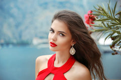 Beautiful girl with red lips, long wavy hair and fashion earring. S. Brunette with curly hairstyle on nature park background stock photo