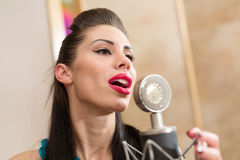 Beautiful girl with red lips in room with microphone Royalty Free Stock Images