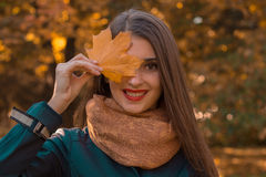 Beautiful girl with red lips in the scarf holds a maple leaf near the eyes and smiles Royalty Free Stock Photography