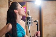 Beautiful girl with red lips sing with microphone. In Recording Studio Royalty Free Stock Photography