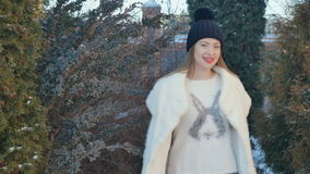 Beautiful girl with red lips in white coat is circling at fir-tree background stock footage