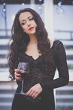 Beautiful girl with red lipstick and glass of red wine. Beautiful young woman with long curly hair drinking red wine in a cafe Royalty Free Stock Photography