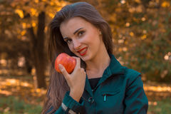 Beautiful girl with red lipstick is holding an Apple in his hand and smiling close-up Stock Photo