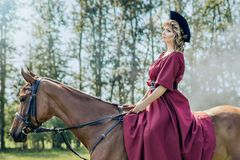 Beautiful woman and brown horse. Beautiful girl in a red long red dress and in a black hat with a cocked hat riding a brown horse stock photography