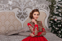 Beautiful girl in red long dress at the Christmas tree Royalty Free Stock Photos