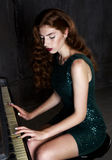 Beautiful girl with red long hair smiling. Bright make-up, red lips. Broad beautiful white smile. The green dress with sequins. Portrait of beautiful girl with Stock Images
