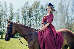 Beautiful girl in a red long red dress and in a black hat with a cocked hat riding a brown horse. stock photography