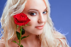 Beautiful girl with red roses in her blond hair Royalty Free Stock Photography