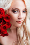Beautiful girl with red roses in her blond hair. Stock Images