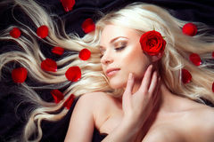 Beautiful girl with red roses in her blond hair. Royalty Free Stock Photos