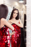 Beautiful Girl in Red Sequin Dress Looking in the Mirror Stock Image