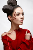 Beautiful girl in a red shirt and shiny hearts on her cheek. Model with a bow on her head and Nude makeup. Image of Valentine`s Day. The beauty of the face Royalty Free Stock Images