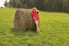 Beautiful girl in a red short shirt with open feet in a meadow o Stock Photos