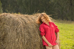 Beautiful girl in a red short shirt with open feet in a meadow o Stock Image