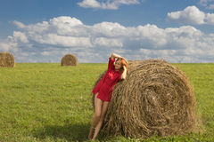Beautiful girl in a red short shirt with open feet in a meadow o Royalty Free Stock Photography