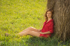 Beautiful girl in a red short shirt with open feet in a meadow o Royalty Free Stock Images
